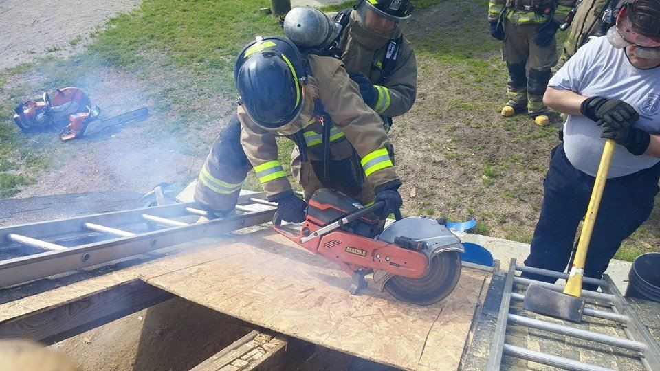 Firefighter Sawing Through a Plank While on a Ladder
