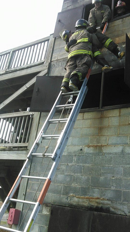 Firefighter at the Top of a Ladder Carrying Another Firefighter