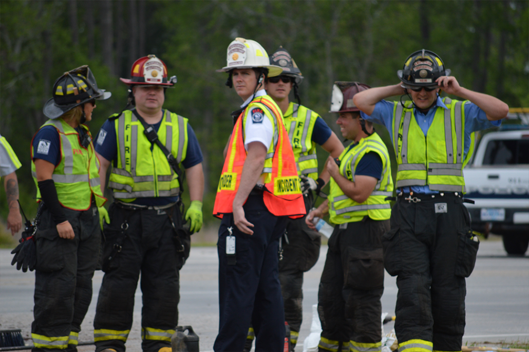 A Group of the Fire and Rescue Team Standing in Vests and Hard Hats